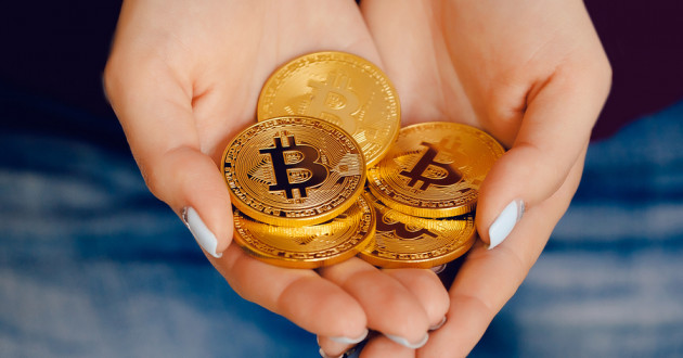 Two hands holding physical coins representing various cryptocurrencies.
