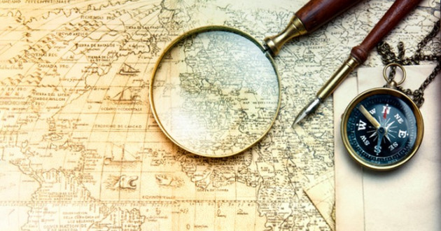 A magnifying glass and compass on an old map.