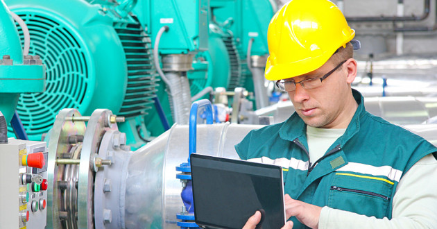 An industrial worker using a laptop.