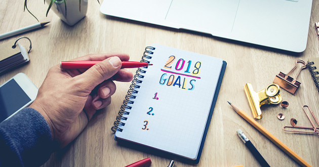 A hand writing a list of New Year's resolutions in a notebook.