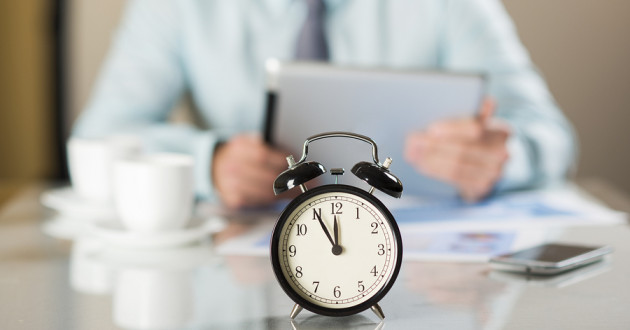 An alarm clock on a desk facing away from a businessperson holding a tablet.