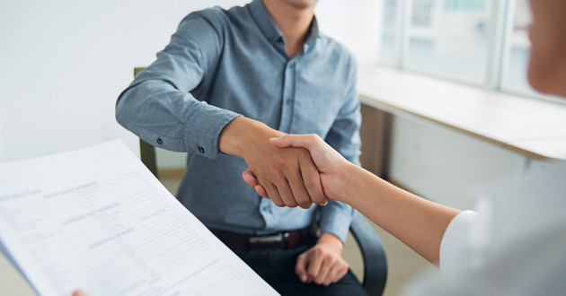 Two people shaking hands during a job interview.
