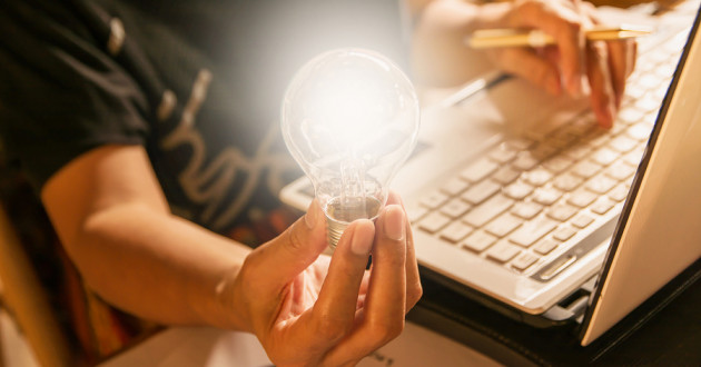 A person holding a lightbulb while using a laptop.