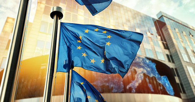 Several EU flags in front of a modern building.