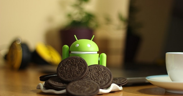 A figurine of the Android mascot behind a pile of cookies.
