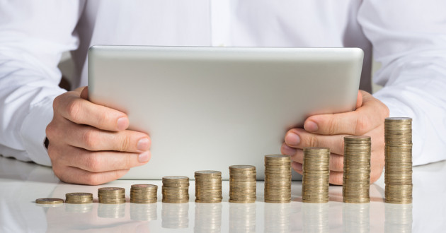 Stacked coins in front of a person using a digital tablet.