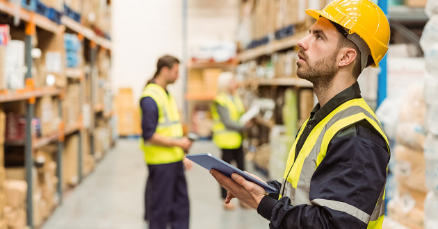 A warehouse manager using a digital tablet.
