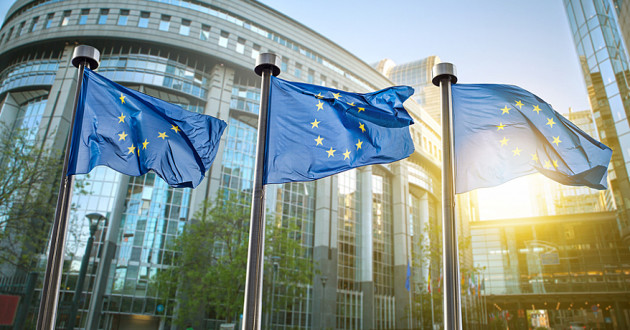 Three European Union (EU) flags in front of a government building in Brussels.