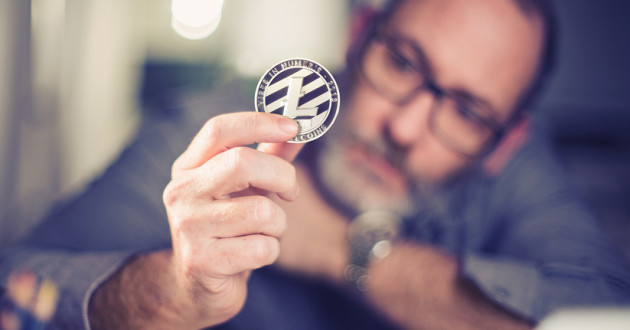 A man holding a physical representation of a Litecoin.