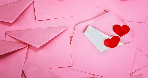 Red hearts coming out of a pink envelope.