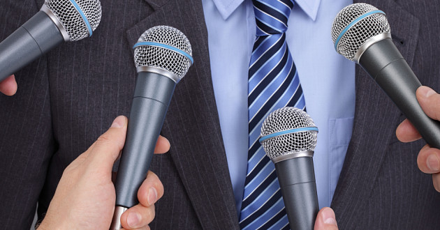 Four hands holding microphones in front of a person wearing a suit.