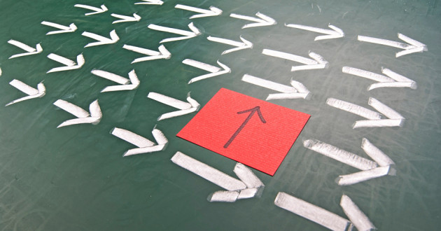One red arrow standing out amid a sea of white arrows pointing in other directions.
