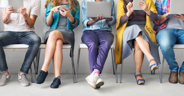 People sitting in chairs while using electronic devices.