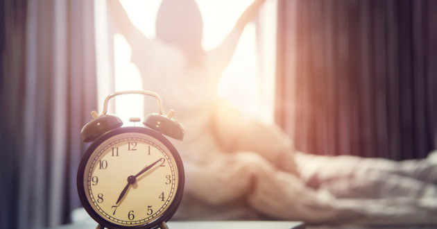 Alarm clock and woman waking up to a good morning.