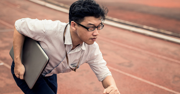 A businessman holding a laptop while running on a track.