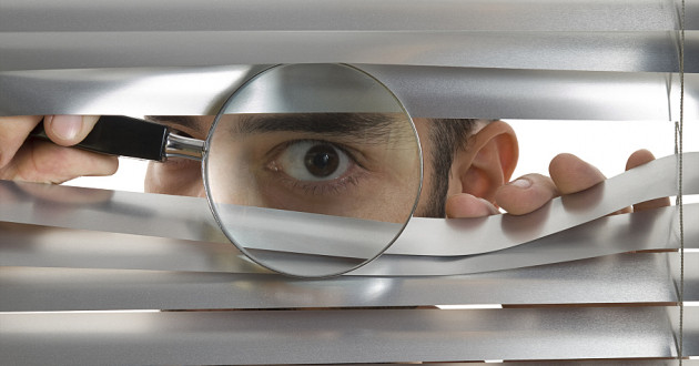 A man peering through window blinds with a magnifying glass.