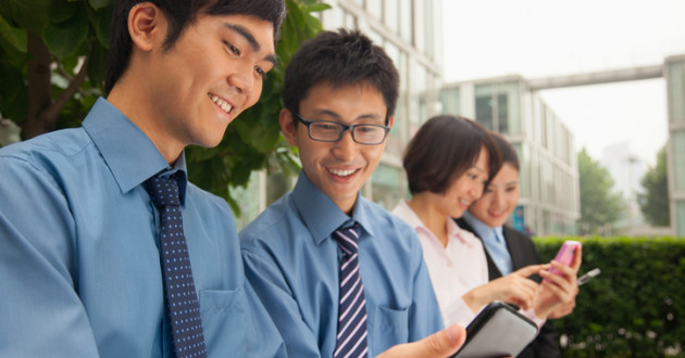 Young business people checking their cell phones.