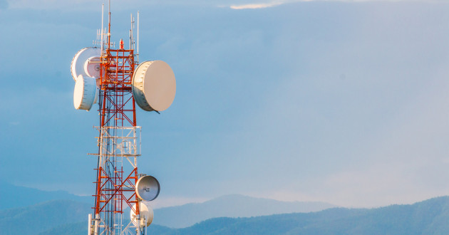 A telecommunications tower in front of a mountain range.