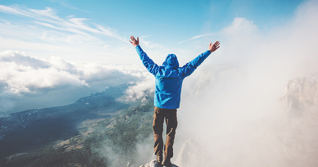 A man raising his arms at the top of a cliff.