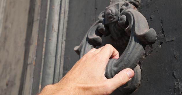 A hand lifting an iron door knocker.