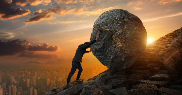 A businessman pushing a boulder up a hill.
