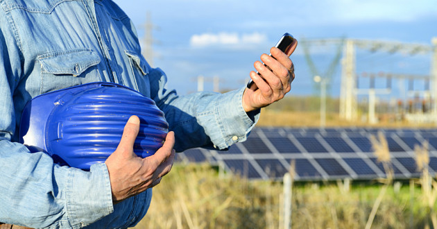 An energy and utilities worker using a smartphone at a solar panel site.