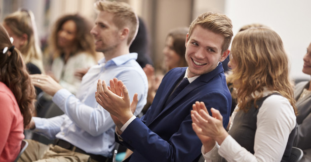 Audience applauding a speaker at a conference.