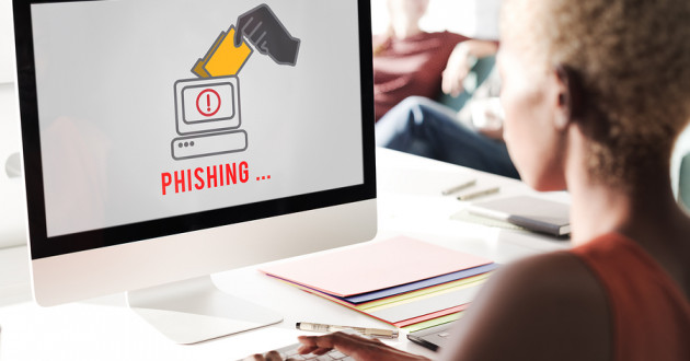 A woman viewing a phishing graphic on a desktop computer in an office.
