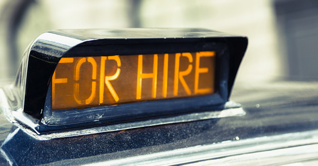 "A ""for hire"" sign on a taxi."