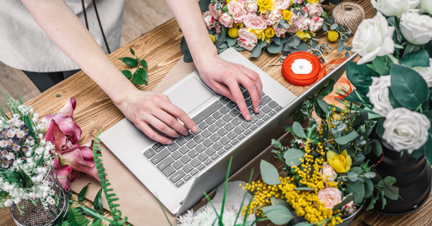 A small business owner using a laptop in a flower shop.