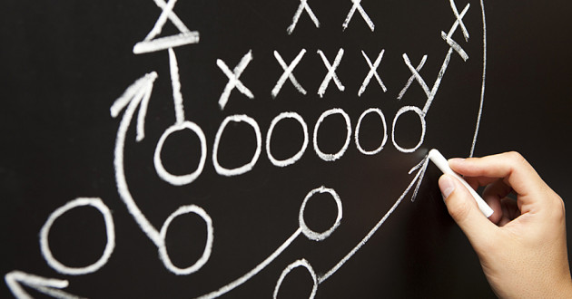 A hand drawing a football play on a blackboard.