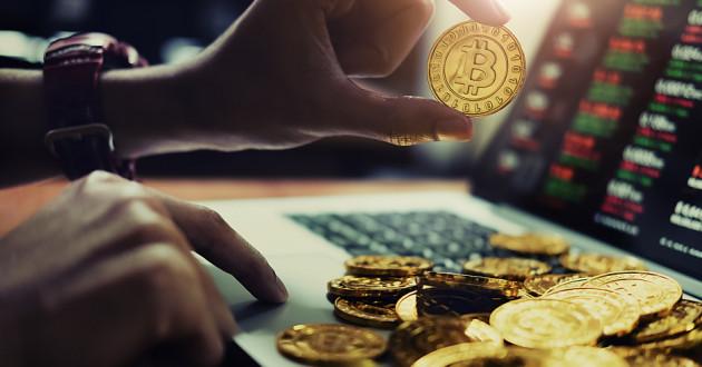 A hand holding a physical representation of a bitcoin: crypto-mining