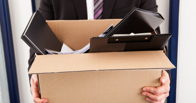 A businessman carrying office supplies in a cardboard box.