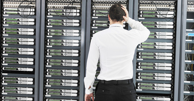 A man standing in front of network servers with a hand on his head: crisis response