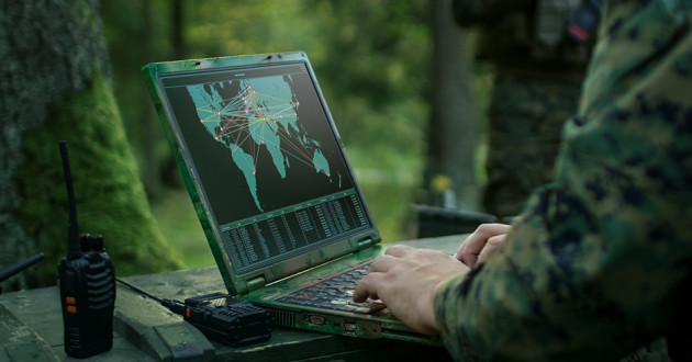 A soldier using a laptop.