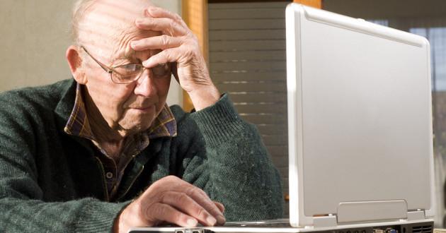 An elderly man using a laptop.