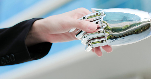 A person shaking hands with a humanoid mechanical hand: AI and cybersecurity