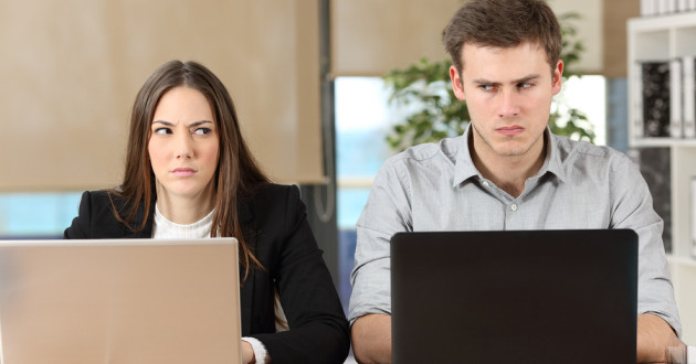 Front view of two angry businesspeople using computers disputing at workplace and looking sideways each other.