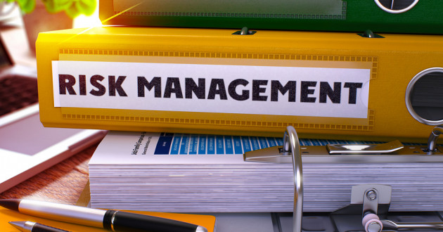 "A binder labeled ""risk management"" on a desk."
