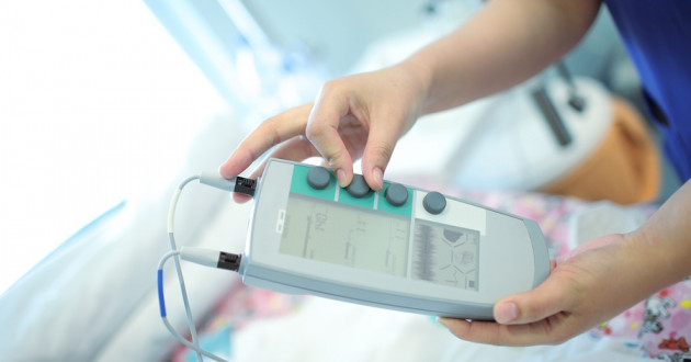 A healthcare professional using an electronic medical device.