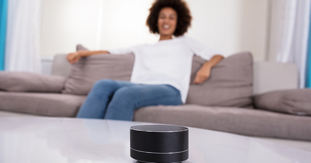 A smart assistant device on a table in front of a woman sitting on a couch.