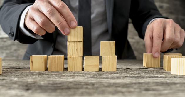 A businessman arranging wooden blocks on a desk.