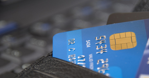 A credit card with an EMV chip sticking out of a wallet.