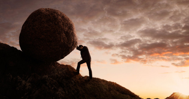 Man struggling to push a large boulder up a hill.