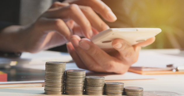 Stacks of coins in front of a person using a smartphone.