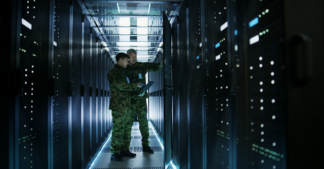 Military personnel working in a data center.