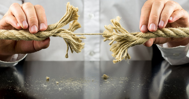 A person holding two ends of a frayed rope.