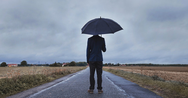 A person standing in the middle of a road holding an umbrella on a cloudy day.