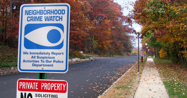 A neighborhood crime watch sign on a suburban road.