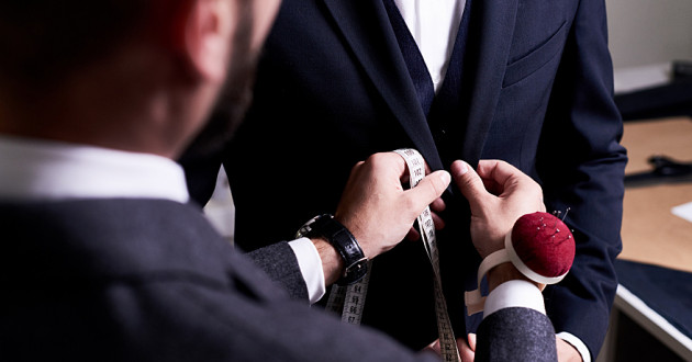 A tailor pinning a suit on a model.
